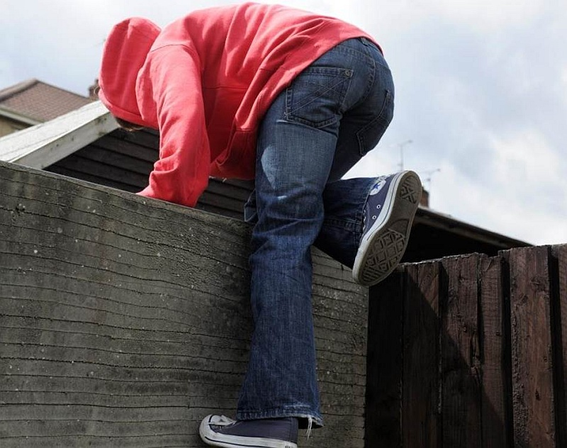 Photo of someone climbing over a wall.
